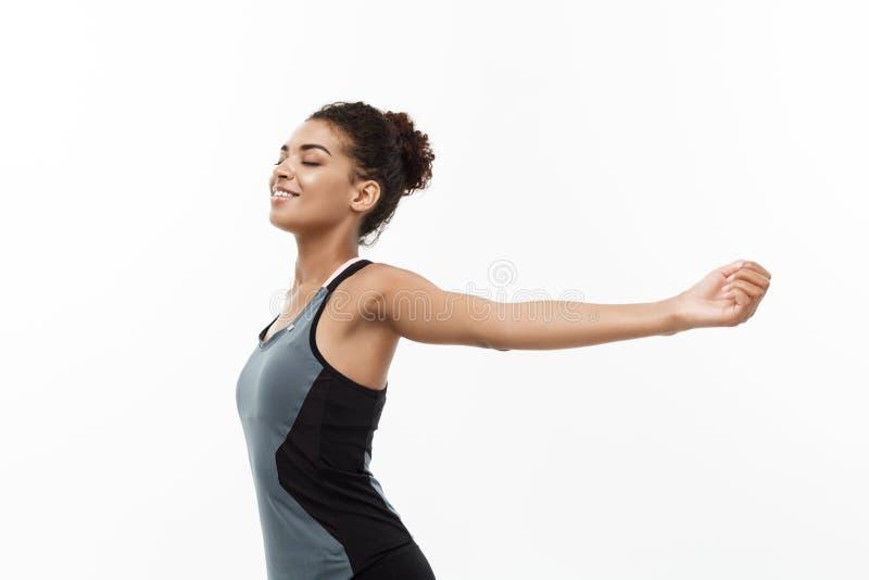 健康和健身概念-年轻美丽的非裔美国人画象用关闭她的手被伸出和注视 免版税库存照片