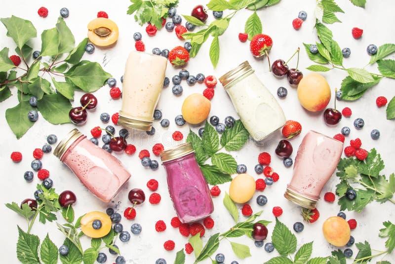 健康和有用的五颜六色的莓果cokctalis、圆滑的人和奶昔用酸奶,新鲜水果和莓果在灰色桌,顶视图上 库存图片