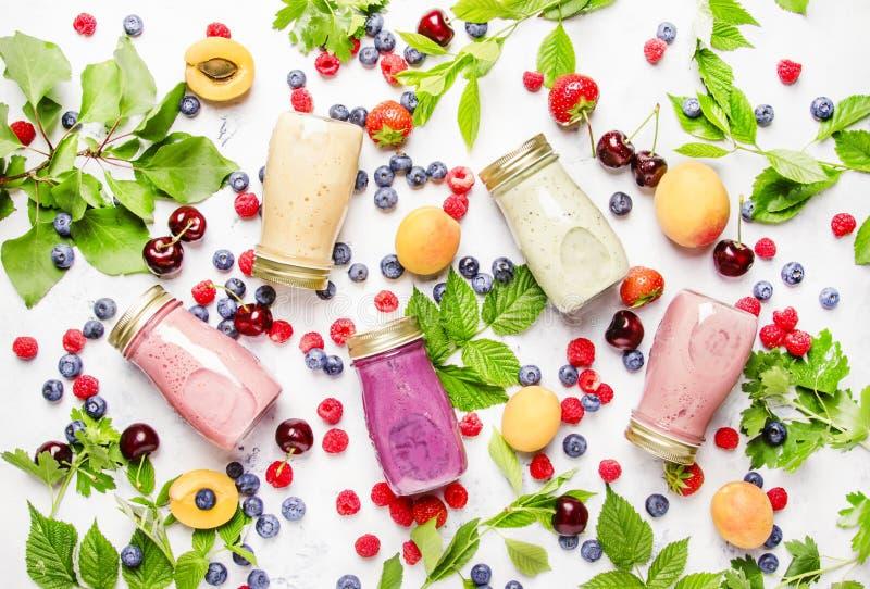 健康和有用的五颜六色的莓果cokctalis,圆滑的人和挤奶 免版税库存图片