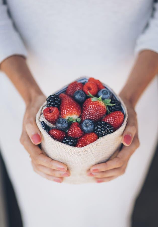 健康和水多的莓果在有白色礼服的妇女的手上 库存照片