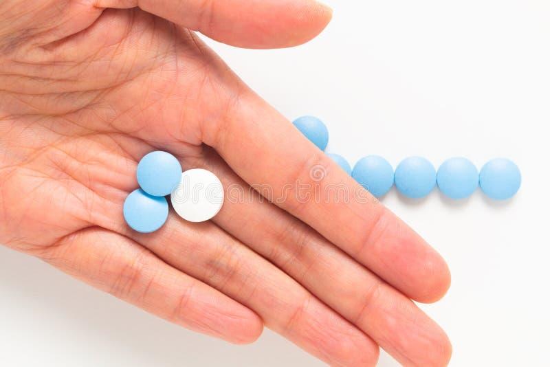 健康和疗程概念蓝色和白色药片在妇女手上服麻醉剂或片剂有拷贝空间的 免版税库存图片