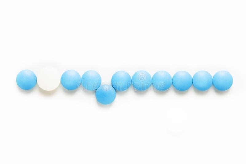 健康和疗程概念蓝色和白色药片服麻醉剂或在白色背景的片剂与拷贝空间 免版税库存图片
