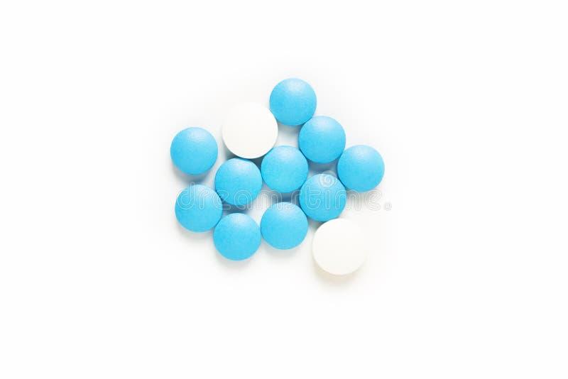 健康和疗程概念蓝色和白色药片服麻醉剂或在白色背景的片剂与拷贝空间 库存照片