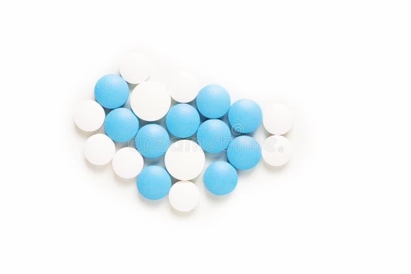 健康和疗程概念蓝色和白色药片服麻醉剂或在白色背景的片剂与拷贝空间 免版税库存照片