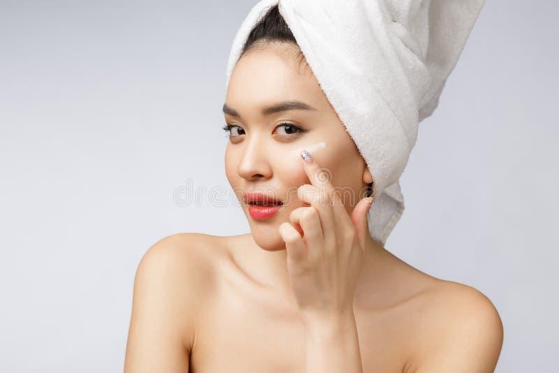 健康和秀丽概念-应用在她的皮肤的可爱的亚裔妇女奶油,在白色 免版税图库摄影