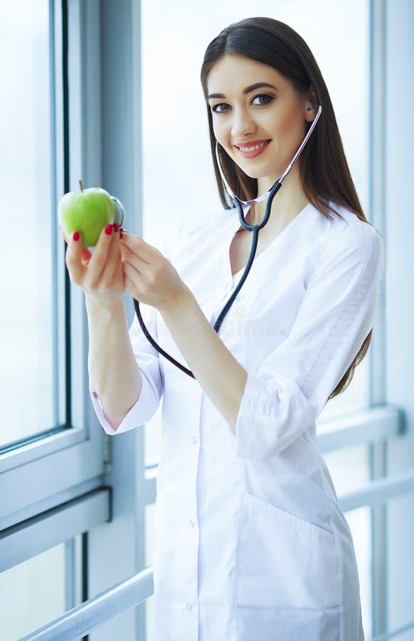 健康和秀丽 营养师拿着新鲜的水果和蔬菜在手上 有美好的微笑的年轻医生 免版税库存图片