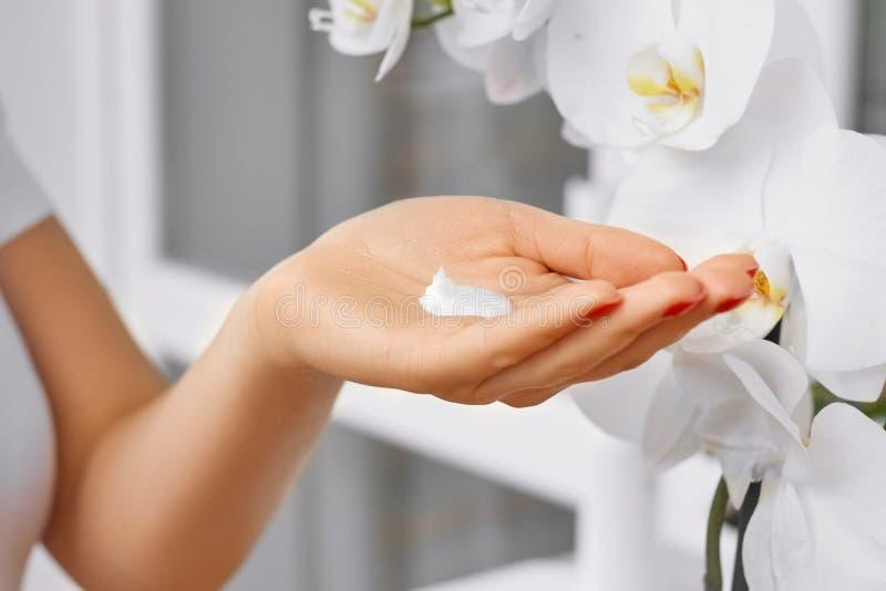 健康和身体关心题材:有白色奶油的美好的女性手在有白色兰花花的轻的晴朗的室 免版税库存图片