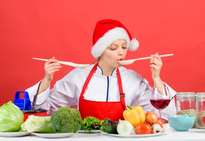 健康圣诞节假日食谱 欢乐菜单概念 妇女厨师烹调举行木匙子的圣诞老人帽子 最佳的圣诞节 库存图片