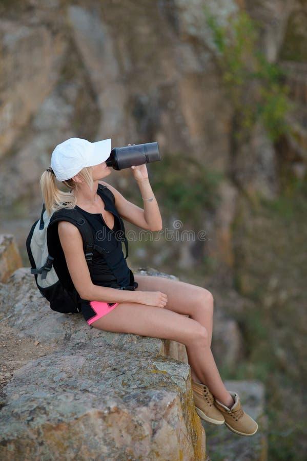 健康在山美好的风景的女孩饮用水  免版税库存照片