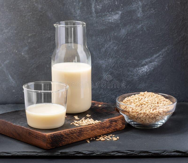 健康在玻璃瓶和玻璃和燕麦种子的素食主义者牛奶店免费燕麦牛奶在灰色背景的玻璃碗 免版税库存照片
