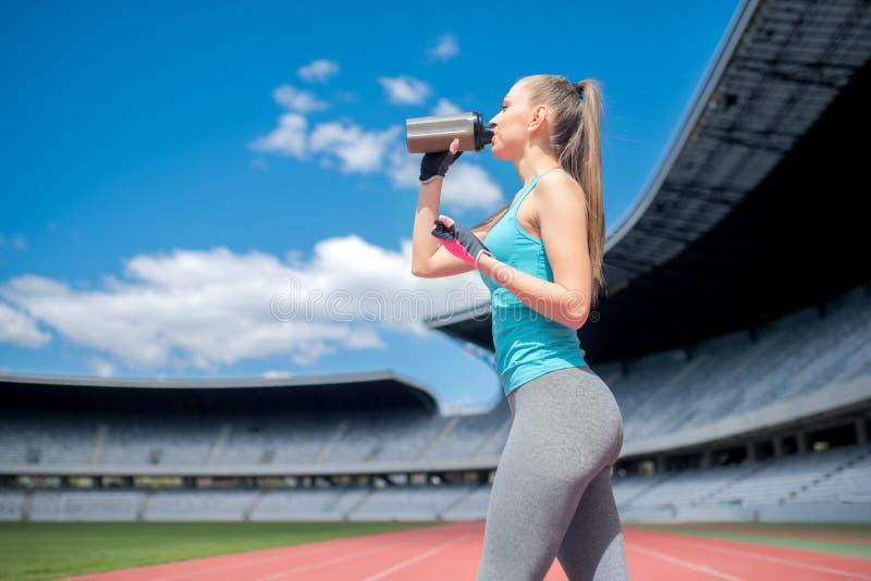 健康在锻炼期间的健身女孩饮用的蛋白质震动在体育场 库存图片