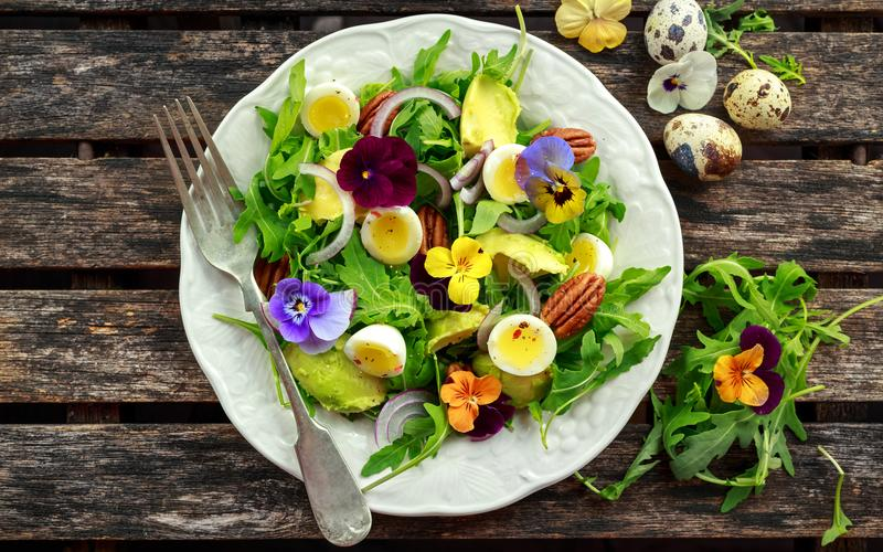 健康夏天沙拉用鹌鹑蛋、鲕梨、胡桃、狂放的火箭、红洋葱和可食的中提琴开花 库存图片