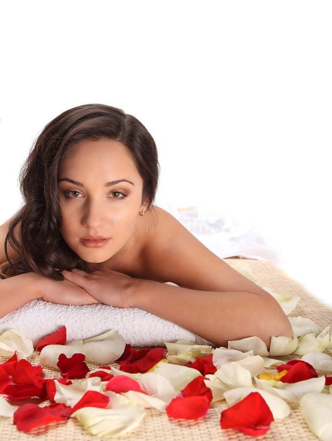 健康天温泉的轻松的妇女,放置在白色毛巾在用玫瑰花瓣装饰的竹桌 库存照片
