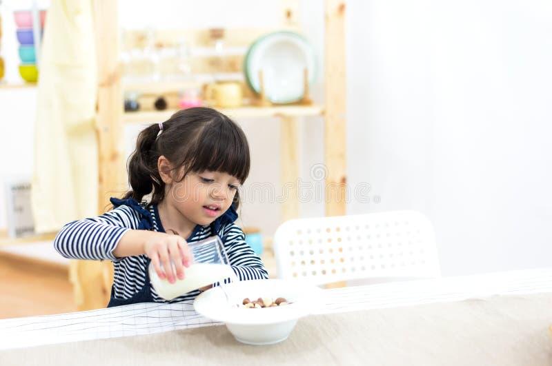健康女孩孩子倒从水罐的牛奶 免版税图库摄影