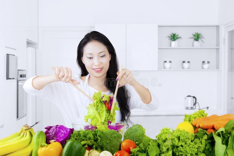 健康妇女活泼的沙拉在厨房里 免版税库存照片
