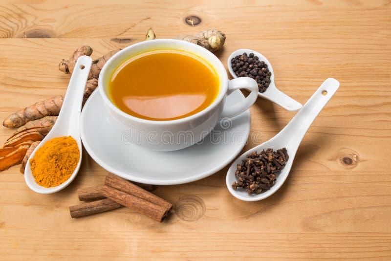 健康姜黄茶用黑胡椒、桂香、丁香和杜松子酒 库存照片