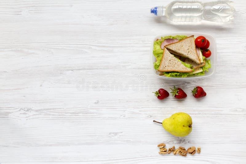 健康学校午餐箱子用新鲜水果、核桃、有机菜三明治和瓶在白色木背景的水, 库存照片