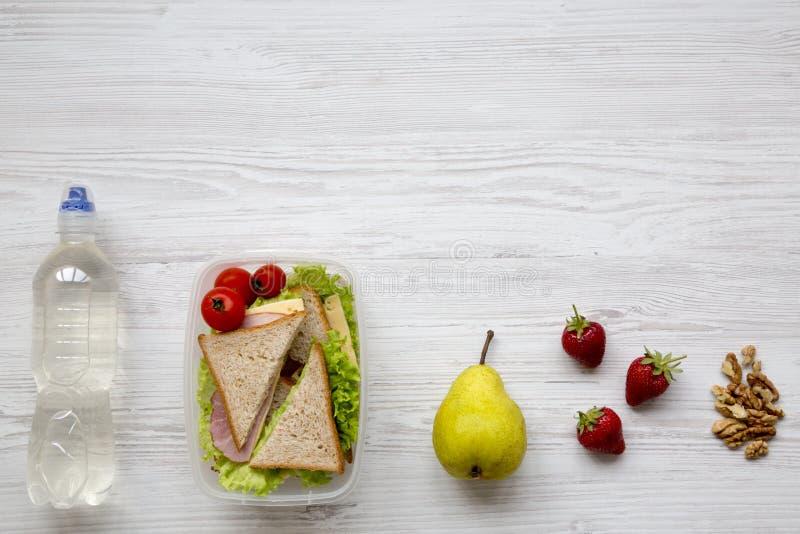 健康学校午餐箱子用新鲜的有机菜三明治、核桃、果子和瓶在白色木背景的水, 图库摄影