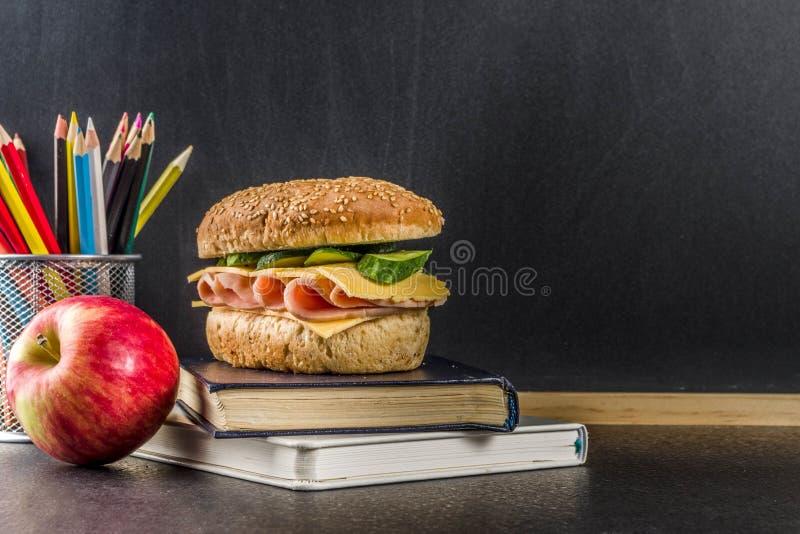 健康学校食物概念,午餐用苹果,三明治,书a 免版税库存图片