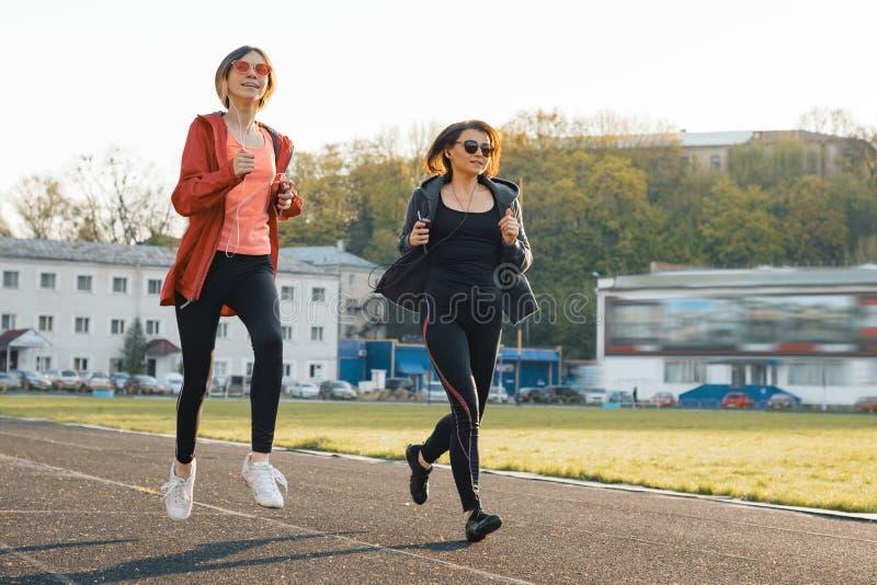 健康家庭生活方式、跑在体育场的健身母亲和青少年的女儿在春天晴朗的晚上 库存图片