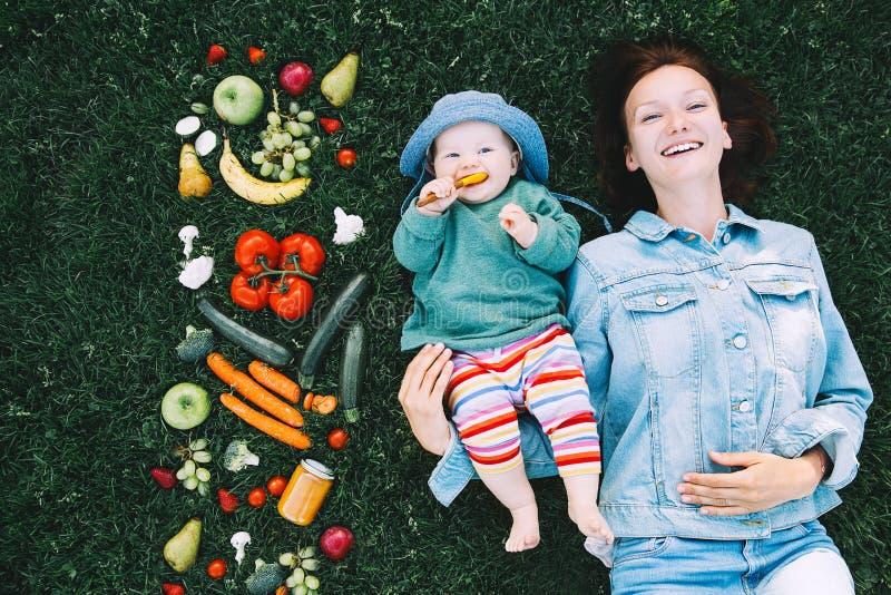 健康家庭营养 母亲和婴孩用果子和vegeta 图库摄影