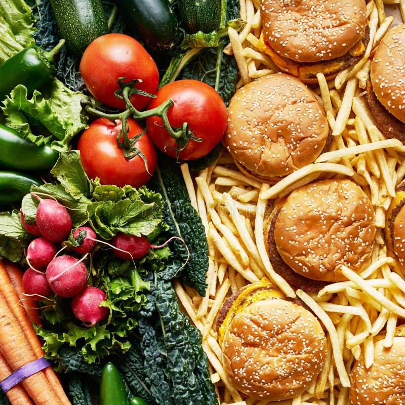 健康对在两堆的不健康的食物 免版税库存照片