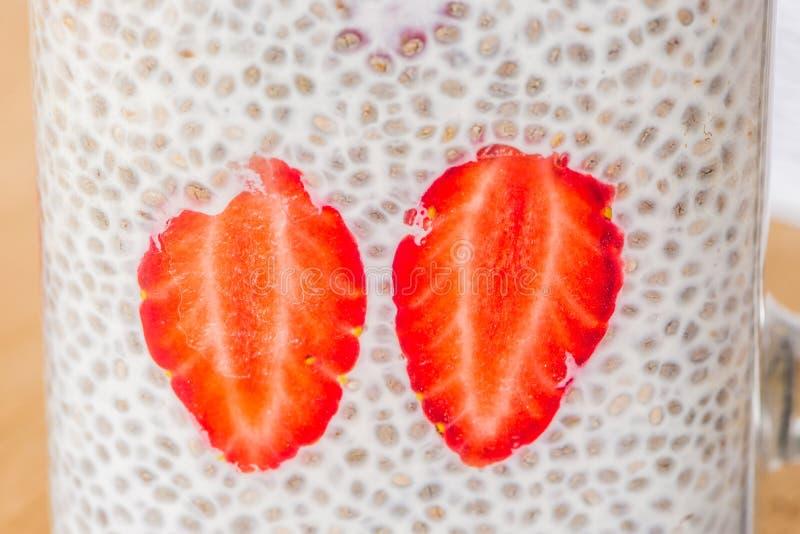 健康层状点心用chia布丁、草莓和忍冬属植物在一个金属螺盖玻璃瓶在土气背景 免版税图库摄影