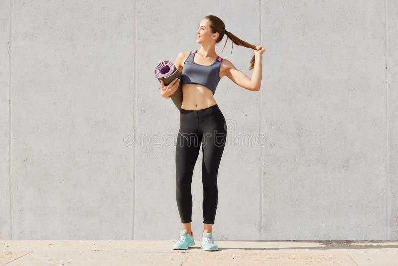 健康年轻女人全长照片拿着瑜伽席子的运动服的,接触她的马尾辫,在训练以后被拍摄, 图库摄影