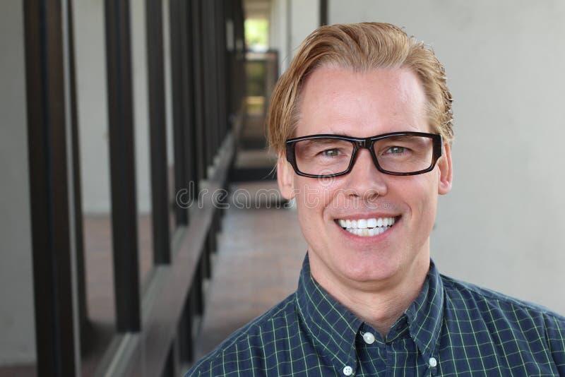 健康微笑 漂白的牙 美好的微笑的年轻人画象关闭  在现代走廊背景 笑 免版税库存图片
