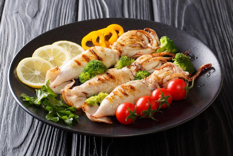 健康快餐:烤乌贼用蕃茄,硬花甘蓝,柠檬和 库存图片