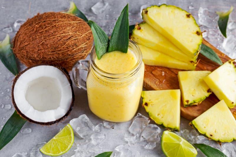 健康成熟黄色菠萝、椰子、圆滑的人与切片石灰和冰 免版税库存照片