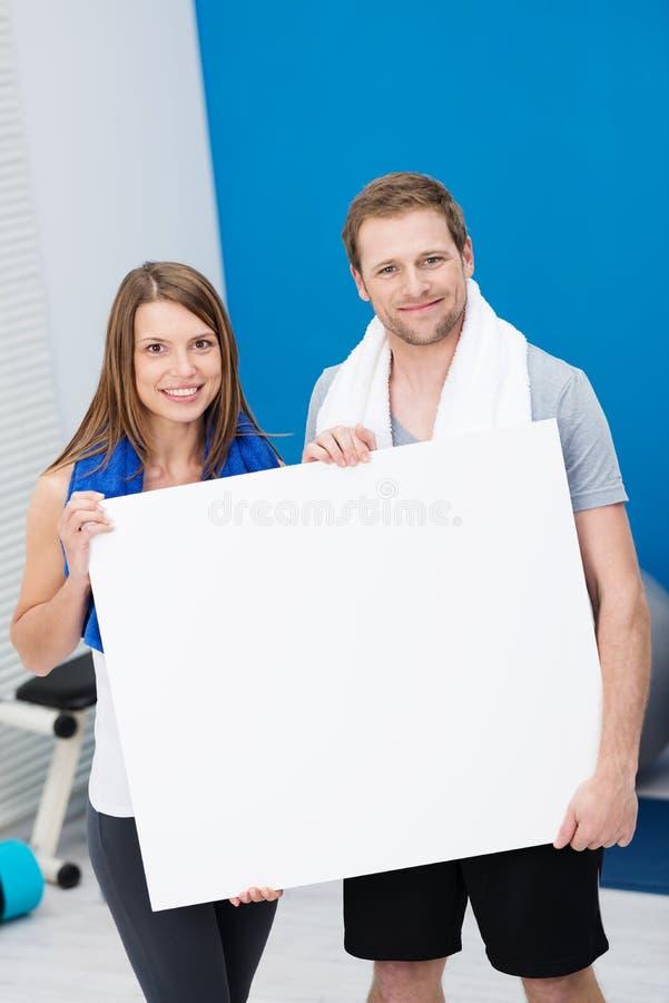 健康拿着一个空白的标志的适合年轻夫妇 库存照片