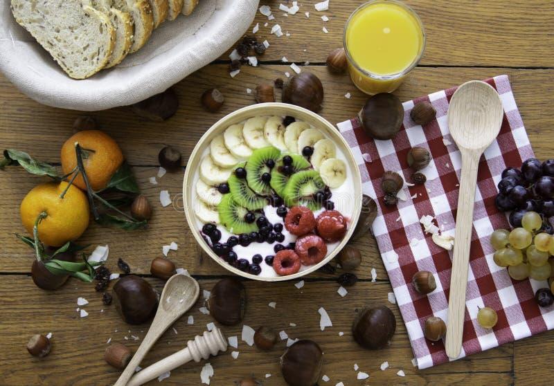 健康新鲜的早餐用面包酸奶果汁和坚果在木桌上 免版税库存照片