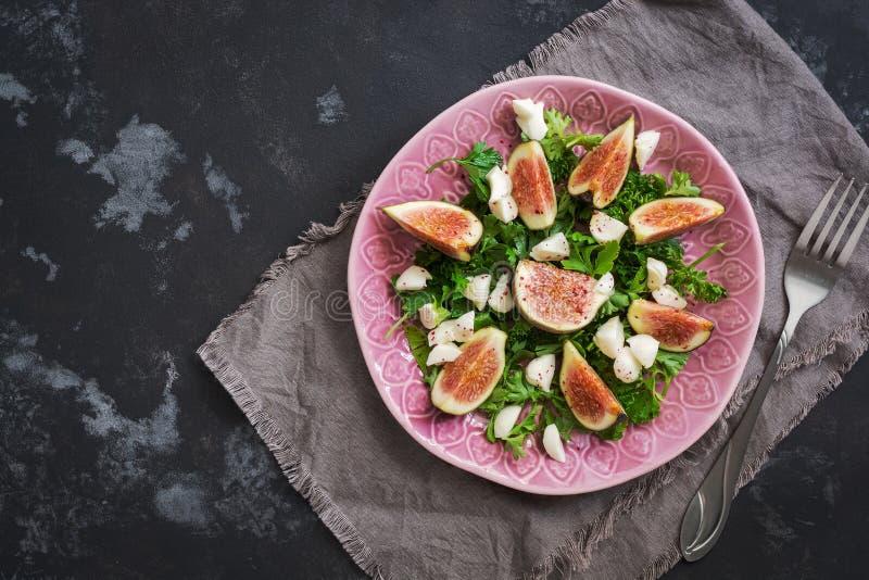健康无花果沙拉、希腊白软干酪和新绿色在黑土气具体背景 从上面,平的位置的看法 免版税库存图片