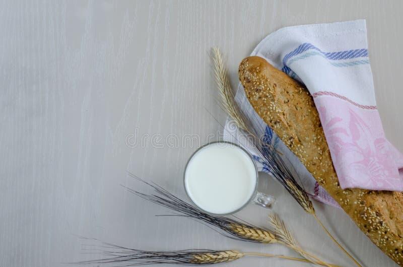健康早餐、食物在村庄,新鲜的多五谷面包和一个杯子牛奶,麦子的小尖峰,燕麦,装饰的大麦 免版税库存照片