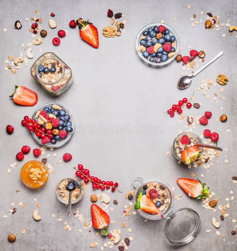 健康早餐圆的框架 各种各样的新鲜的莓果、muesli和坚果在灰色背景 库存照片