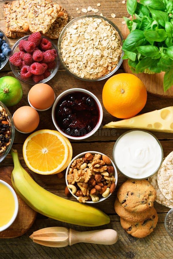 健康早餐成份,食物框架 格兰诺拉麦片,鸡蛋,坚果,果子,莓果,多士,牛奶,酸奶,橙汁 免版税库存照片