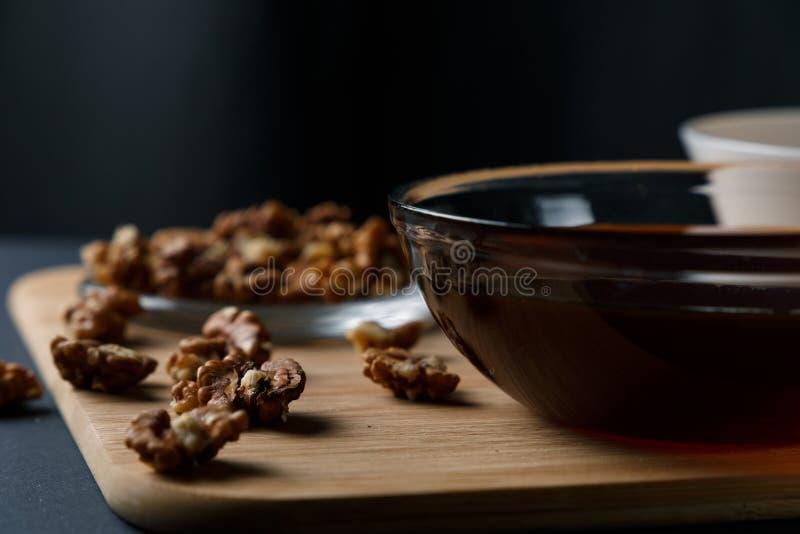 健康早餐成份:蜂蜜,核桃,在黑暗的背景的燕麦粥 免版税库存照片