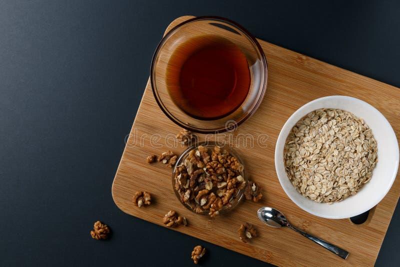 健康早餐成份:蜂蜜,核桃,在黑暗的背景的燕麦粥 E 免版税库存照片