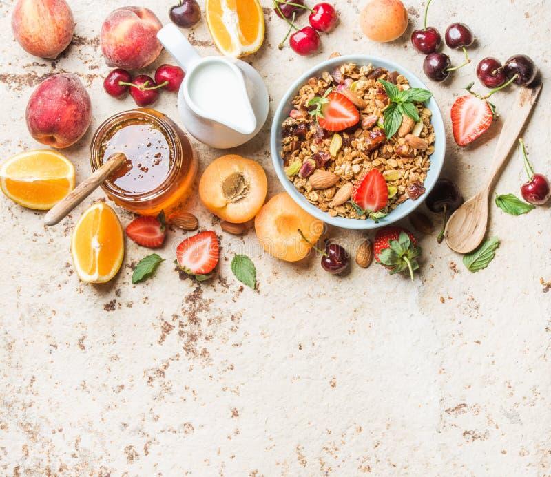 健康早餐成份 在碗的燕麦格兰诺拉麦片有坚果、草莓和薄菏的,在水罐,在玻璃瓶子的蜂蜜的牛奶 免版税库存图片