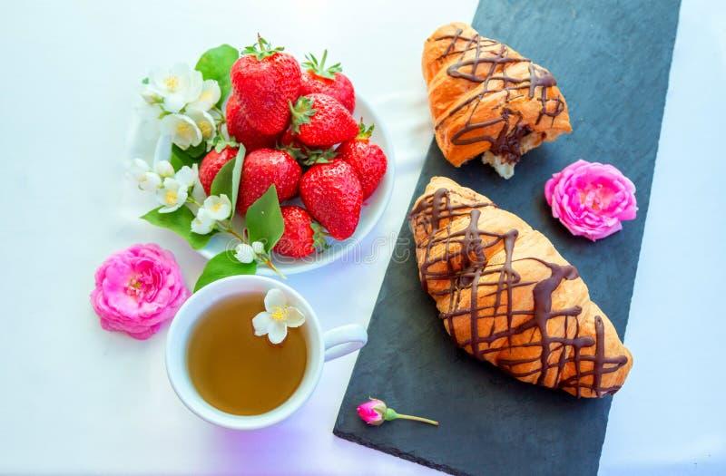 健康早餐或快餐–茶、新月形面包、草莓和花 库存照片