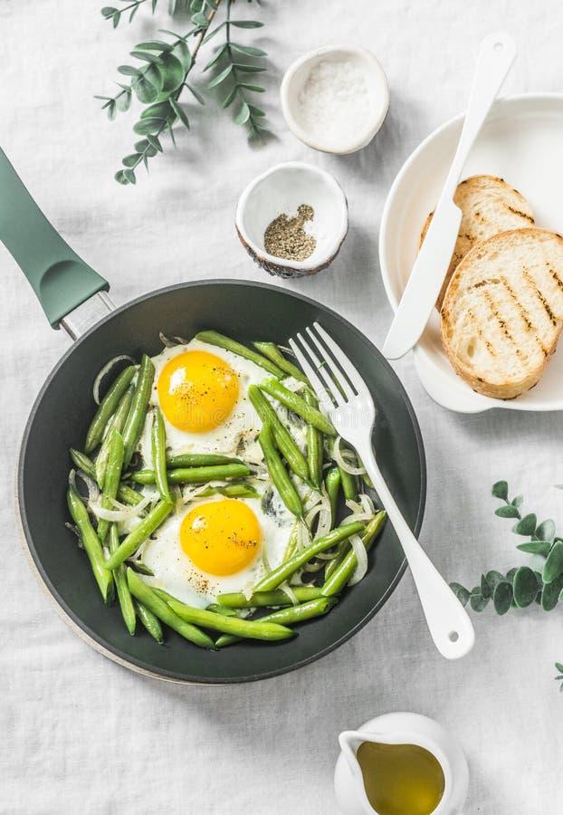 健康早餐或快餐-一个煎蛋用在平底锅的青豆在轻的背景 免版税库存图片