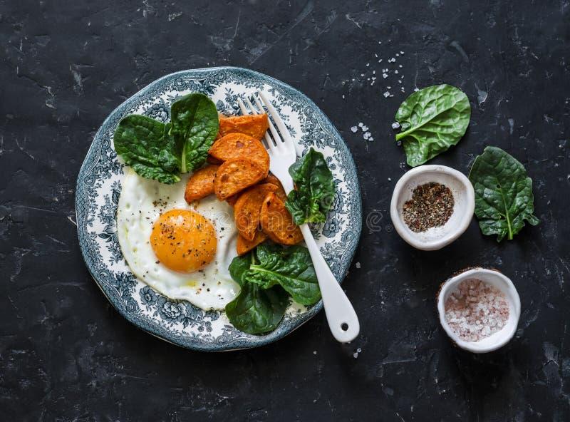 健康早餐或快餐-煎蛋、被烘烤的白薯和菠菜在黑暗的背景 免版税库存图片