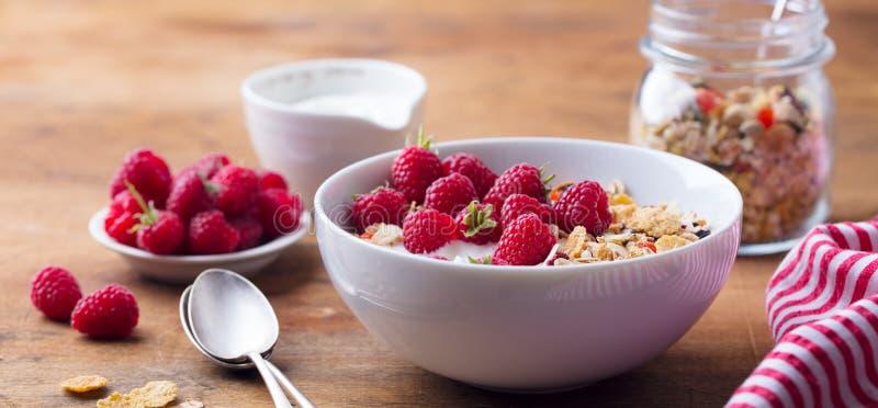 健康早餐新鲜的格兰诺拉麦片、muesli用酸奶和莓果在木背景 免版税库存照片