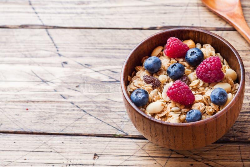 健康早餐新鲜的格兰诺拉麦片、muesli用酸奶和莓果在木背景 r 免版税库存图片