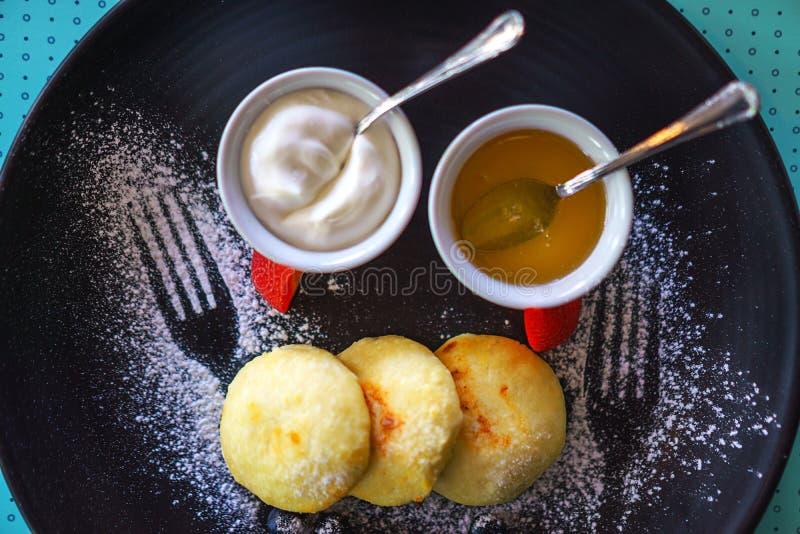 健康早餐村庄乳酪蛋糕俄国sirniki用蜂蜜和酸性稀奶油早餐在蓝色背景 图库摄影