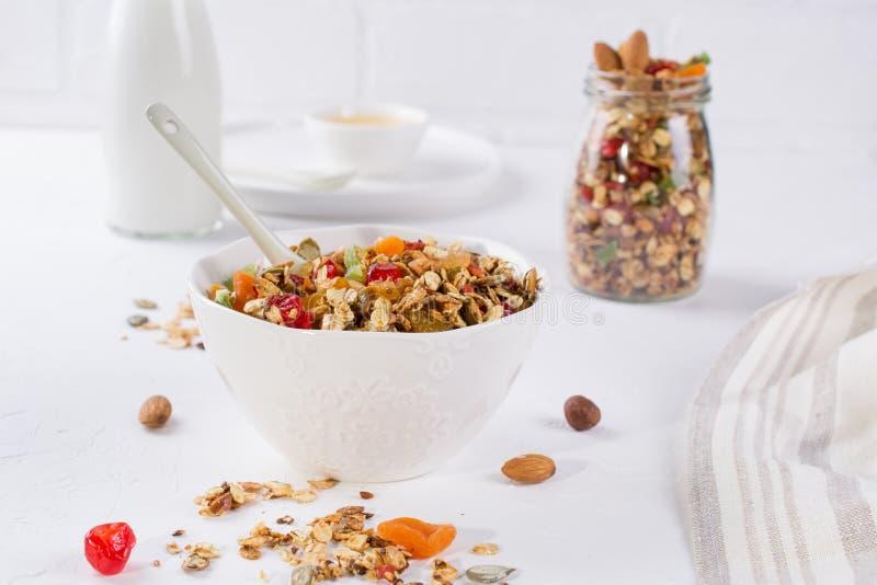 健康早餐概念 在白色陶瓷碗和玻璃瓶子的被烘烤的格兰诺拉麦片 免版税库存图片