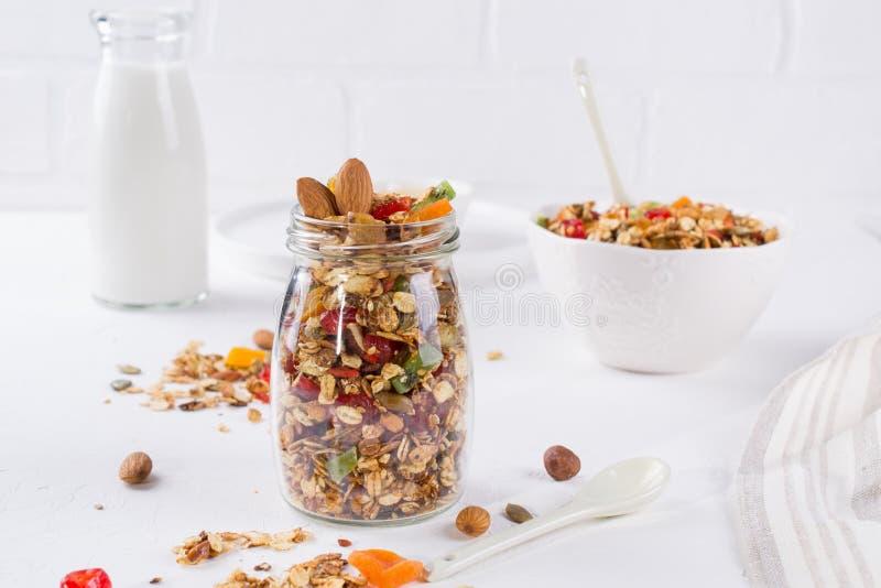健康早餐概念 在白色陶瓷碗和玻璃瓶子的被烘烤的格兰诺拉麦片 免版税库存照片