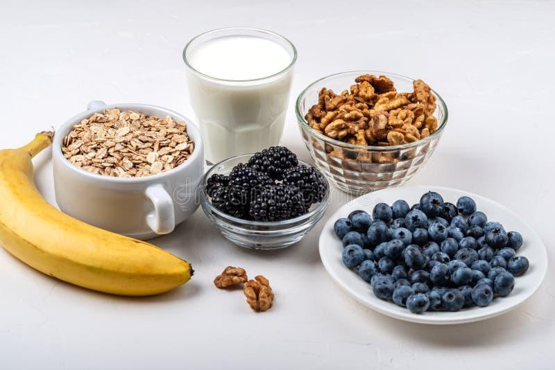 健康早餐燕麦粥的成份,牛奶,黑莓,蓝莓,香蕉,在白色背景的核桃 库存图片