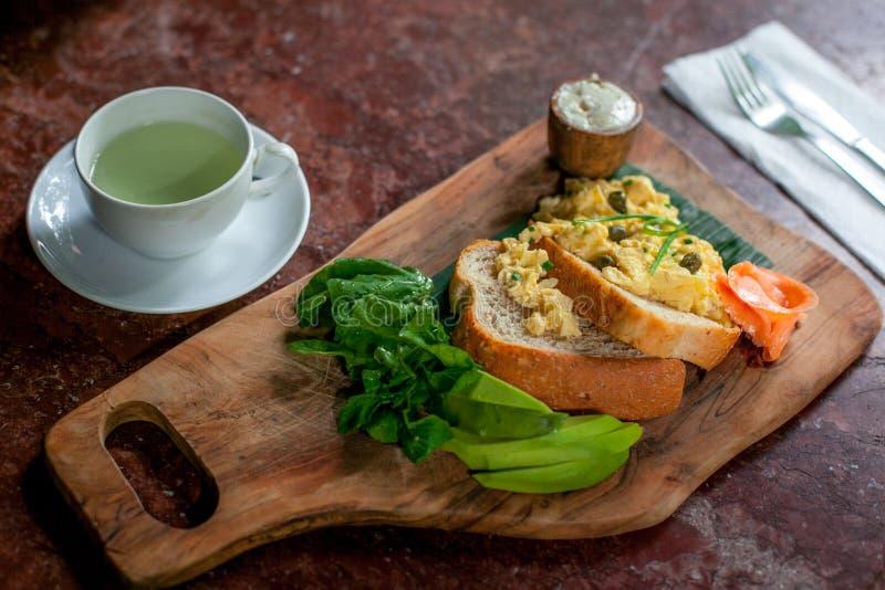 健康早餐用全麦面包多士和炒蛋与avokado,乳酪和三文鱼在切板和绿茶 图库摄影